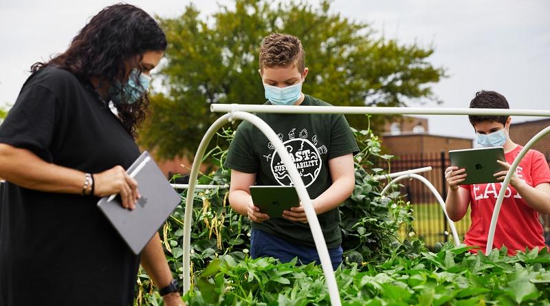 Jodie Deinhammer (izquierda), profesora de ciencias en el centro Coppell Middle School East y Apple Distinguished Educator, usa el iPad en la primera clase de jardinería del curso. Los alumnos pueden visitar el jardín por su cuenta mientras la clase se imparte virtualmente.